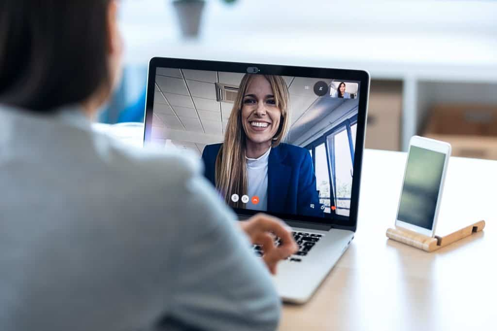 Female employee speaking on video call with her colleague on online briefing with laptop at home.